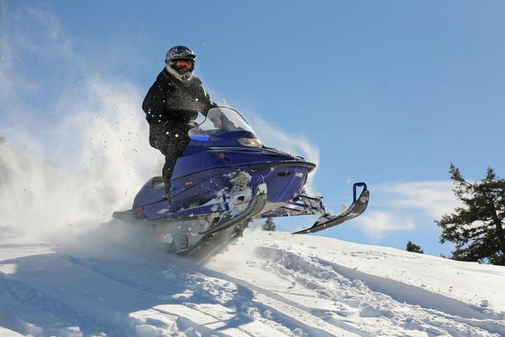 man speeding on a snowmobile